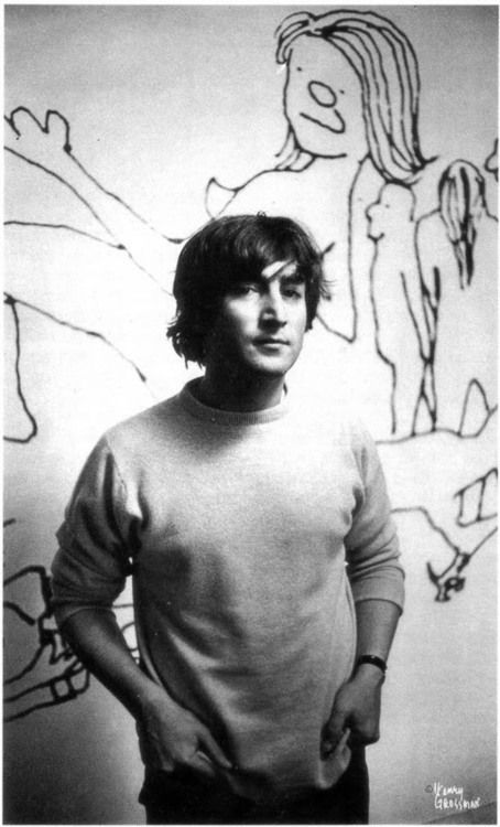 John Lennon stands in front of his artwork.