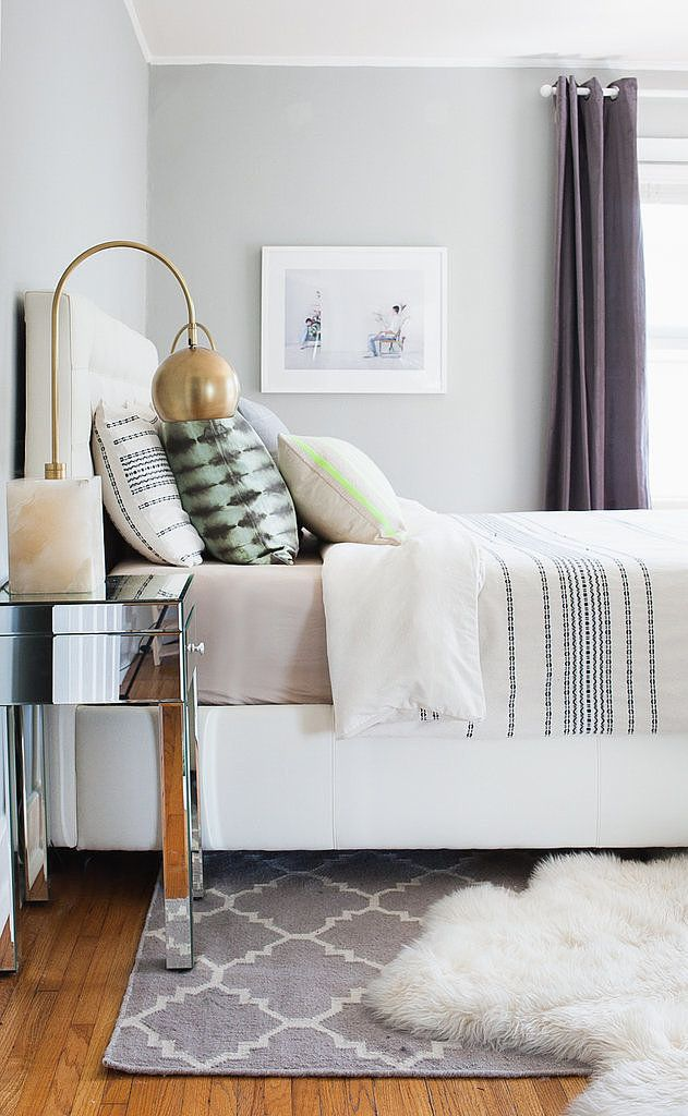 A cozy bedroom with texture, pattern, and a mirrored side table with a modern table lamp