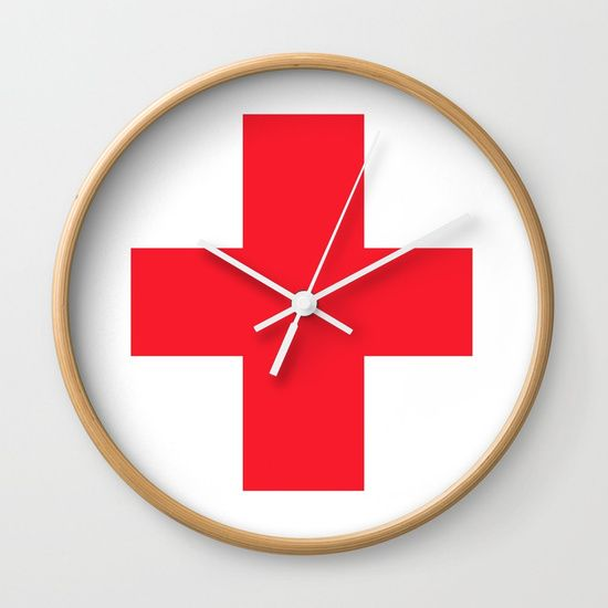 """Red medical first aid cross. Available in natural wood, black or white frames, our 10"""" diameter unique Wall Clocks feature a high-impact plexiglass crystal face and a backside hook for easy hanging. Choose black or white hands to match your wall clock frame and art design choice. Clock sits 1.75"""" deep and requires 1 AA battery (not included)."""