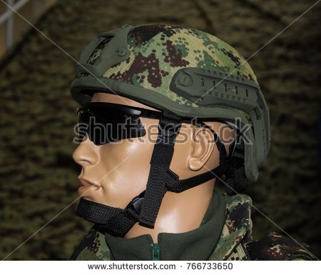 Green camouflage military combat helmet with glassses.