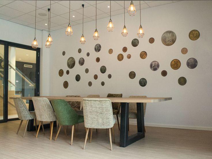 Muntenwand van oude guldens en centen met een knipoog naar de smokkelperiode in Overdinkel. Maatwerk tafel en oude cocktail stoelen.  Interieurontwerp door Evelien Lulofs voor 't Trefhuus: het Kulturhus in Overdinkel.