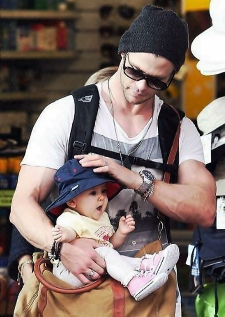 It looks like Chris Hemsworth is trying to stuff his baby into his bag. Still love him