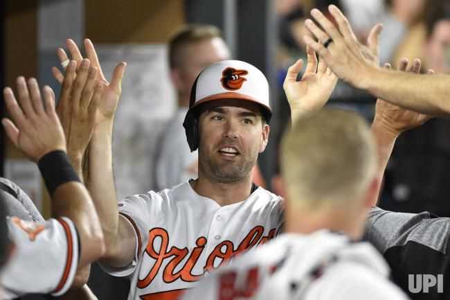 Baltimore Orioles Seth Smith (C) is congratulated in the dugout after scoring against the Texas Rangers on a single by Manny Machado during…