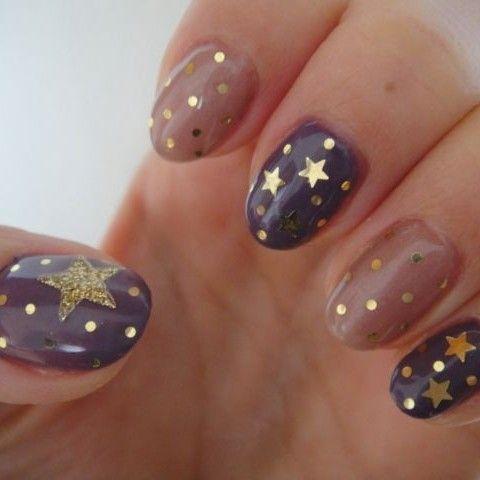 Preciosa manicura de uñas en color marrón y morado, adornadas con diseños de estrellas doradas y lunares.