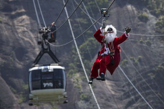 Not to Safe.  A man dressed as Santa Claus zip lines away from Sugar Loaf mountain after riding on top of a cable car in Rio de Janeiro, Brazil, Thursday, Dec. 18, 2014.