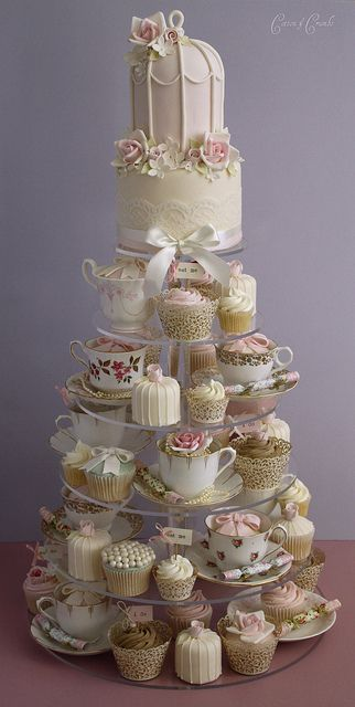 I think the top is hideous, but this is what I mean by less cake, more cupcake. This is too elaborate (all the extras here would cost too much - who has antique china cups just lyin' around?) but if we did a smaller cake like this topper and then did the pails with rose cupcakes...? Just a thought.