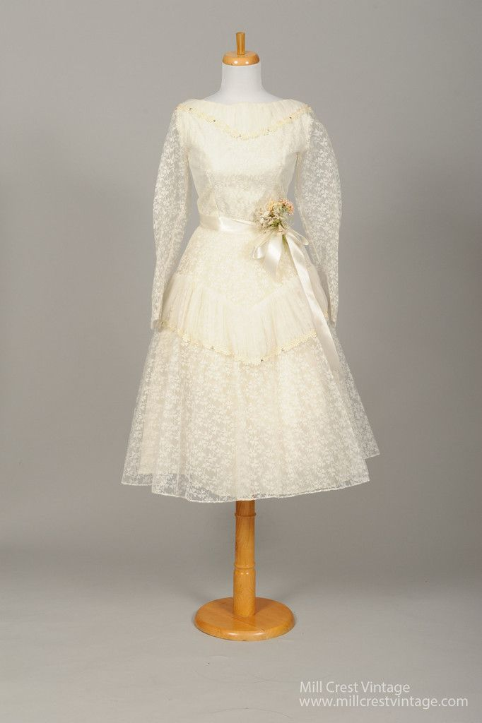 Designed in the 50's, this adorable vintage wedding dress is done in a white lace with a cool shamrock design over a layer of tulle with a taffeta lining and an additional paper lining in the skirt. T