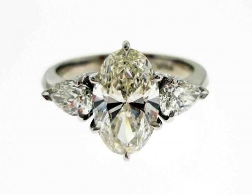 An 18ct White Gold and Diamond Trilogy Ring with an Oval Cut Center Stone and Two Pear Shaped Side Stones