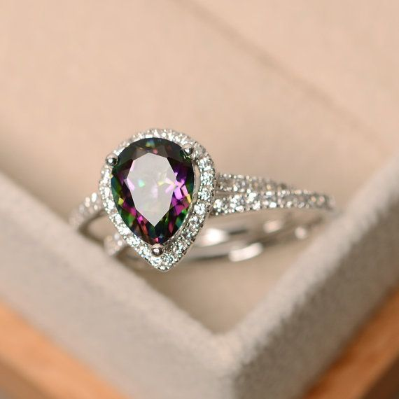 This halo ring features a 7*9mm pear cut mystic topaz and sterling silver finished with rhodium. Customization is available. It is made by hand, and it will take about 7 days to finish the ring after your payment is completed. Any question, just let me know. :) My shop homepage: https://www.etsy.com/shop/LuoJewelry?ref=l2-shopheader-name
