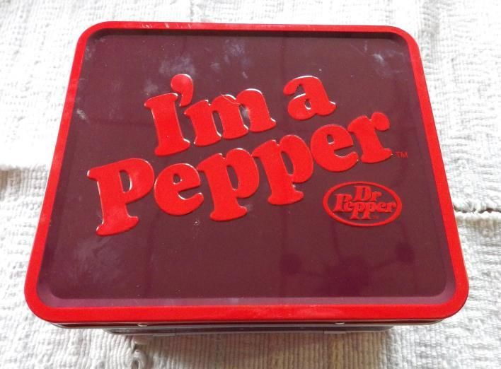 "From the Dr. Pepper Collection. Dr. Pepper I'm a Pepper Lunch Box. This fun lunch box is a red full-sized retro metal lunch box. Thermos not included. Features a tossed star design and the Dr. Pepper I'm a Pepper logo. Measures 8"" x 7""."