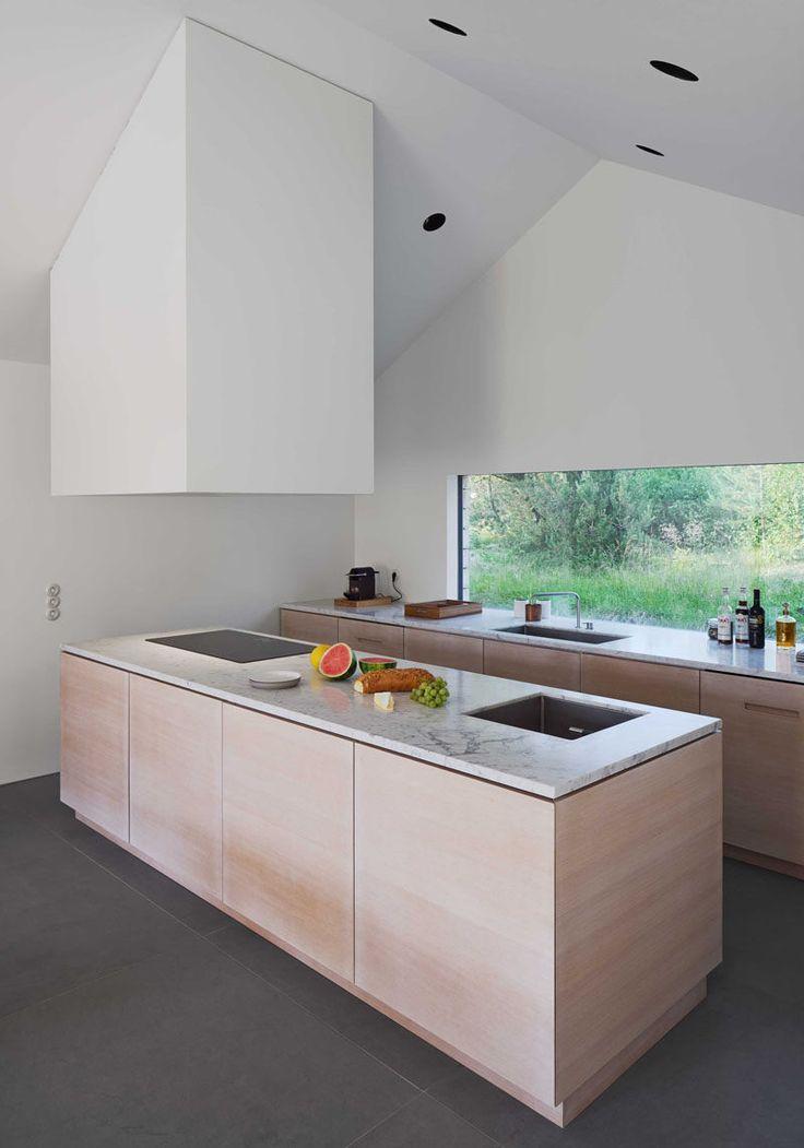 In questa moderna cucina in legno chiaro e pietra, ci sono soffitti alti rendendo lo spazio si sentono alto e aperto.  Una grande finestra permette di vista della vita all'aria aperta e la luce naturale di inondare il piano di lavoro.