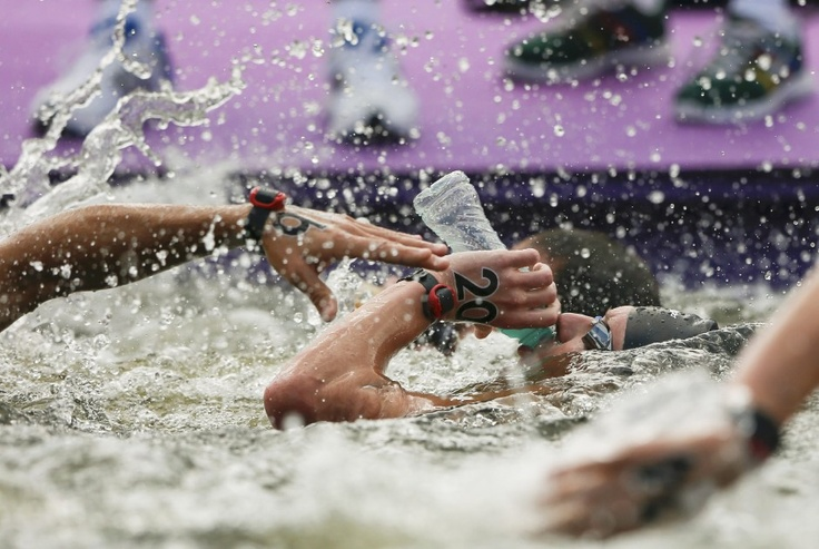 """""""Water, Water Everywhere..."""" Alex Meyer of the U.S. drinks as he competes in the men's 10km marathon swimming at Hyde Park during the London Olympic Games"""