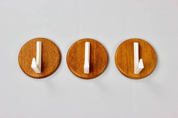 Vintage Garderobenhaken von Holz - typisch 60er Jahre  Die Garderobenhaken bestehen aus Holz und Metall. An der Rückseite sind die einzelnen Haken mit 2 Schrauben sehr stabil an der Wand zu montieren, daher auch super geeignet für schwerere Kleidungsstücke.  Design Danish Modern, Eames Ära.  Guter Vintage Zustand. Schiebespuren von den Aufhängern der Kleiderbügel (s.Fotos)  Maße, einzelner Haken: Länge x Breite x Höhe 10 cm (3.93 inch) x 10 cm (3.93 inch) x 7,5 cm (2.95 inch)…