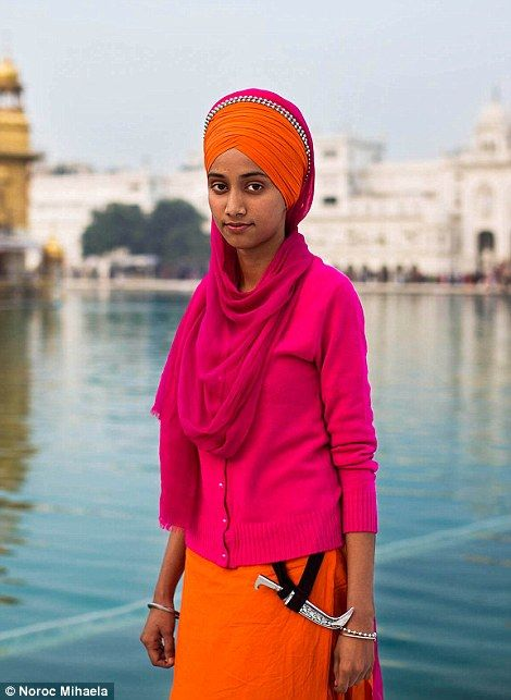 A Sikh woman at the Golden Temple, in Amritsar is seen wearing a colourful turban and the kirpan, the short dagger that symbolises a Sikh's duty to come to the defence of those in peril.