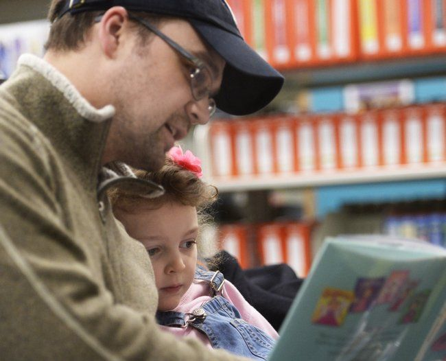 Andrew Sudduth of Schenectady helps his 4-year-old daughter Rose Sudduth to read her very first book at the Phyllis Bornt Branch Library and Literacy Center on State Street at the Grand Opening Saturday, February 27, 2016.