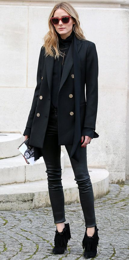 Olivia Palermo in a double-breasted oversize black blazer layered over a black turtleneck, inky skinnies, and fringed booties.