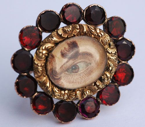 Georgian eye miniature brooch, circa 1820, watercolour on card, set to a gold frame with flat-cut garnet surround and under crystal. Immaculate condition. For similar eye miniature, see Royal Collections, Stockholm, [hair bracelet circa 1820, with eye miniature: