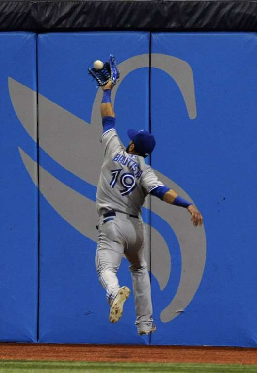 Snagging the fly -  Toronto Blue Jays right fielder Jose Bautista grabs a fly ball hit by Tampa Bay Rays' Evan Longoria during the third inning of a baseball game on Oct. 3 in St. Petersburg, Fla  - © Steve Nesius/AP Photo