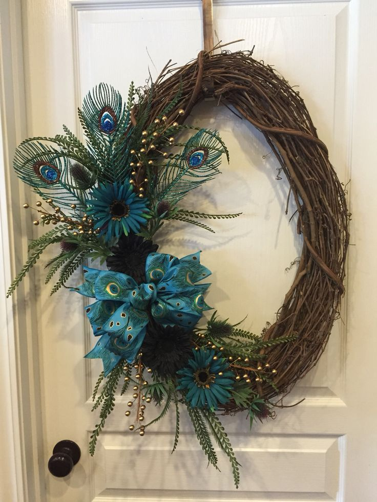 Peacock themed grapevine wreath with black and turquoise daisies with gold accents.