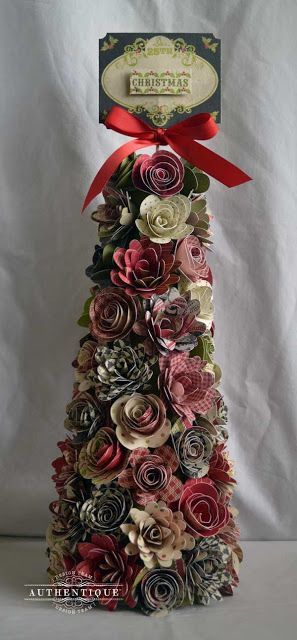 Christmas tree made up of die cut paper flowers, curled and shaped around a centre cone shape with traditional colours of red and green and a sentiment on the top.