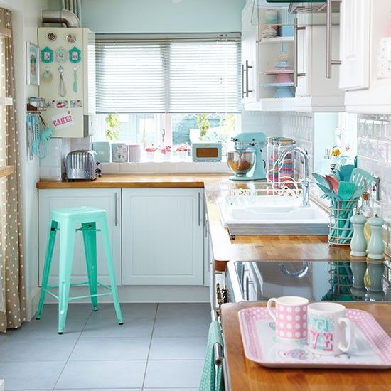 Go for a modern country look with white gloss cabinets and wooden worktops. Pastel green walls and a mix of colourful accessories add interest to this small kitchen.