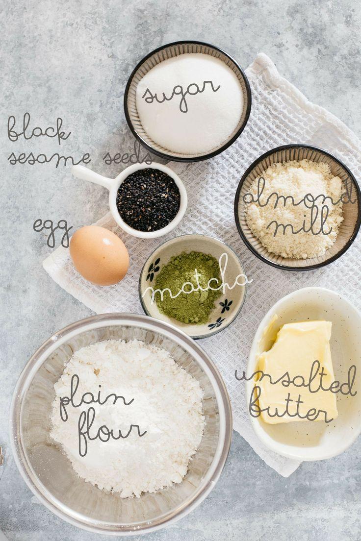 Matcha schwarze Sesamplätzchenbestandteile, einfaches Mehl, Butter, Matcha, Mandelmühle, Ei, schwarze Samen des indischen Sesams und Zucker in den kleinen Schüsseln