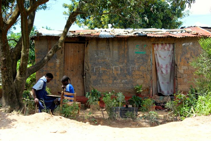 Zambia -two girls play checkers outside their home. Photo by Shelly Vanbinsbergen