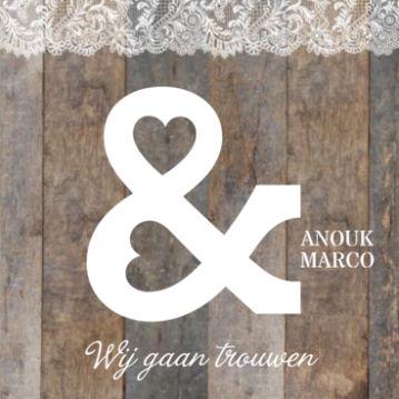 Stoere grove trouwkaart met donker oud hout en bovenaan een strook wit kant. Daar overheen een groot wit &-teken met hartjes als gaten.