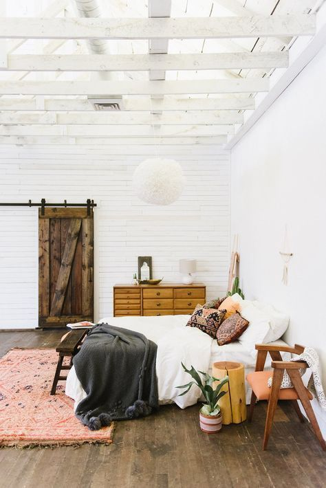 grey throw, blush coral rug, wooden floors, white sheets, sliding door