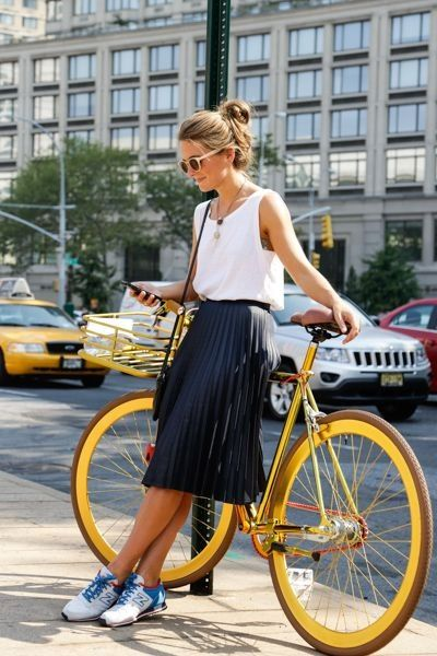 I like the loose fitting top with the pleated skirt here. No sneakers, though.