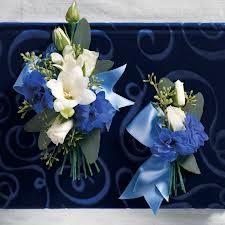 This would be nice for a boutonniere. We like the little freesia/tuberose flower in the middle (on the corsage one) and then the little blue flowers around it)