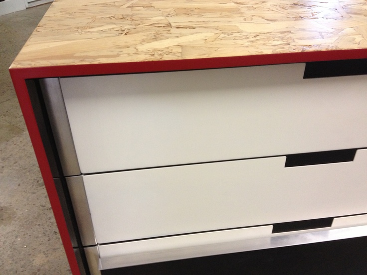 A red lip details the strandboard shell over a white powder-coated steel drawer set