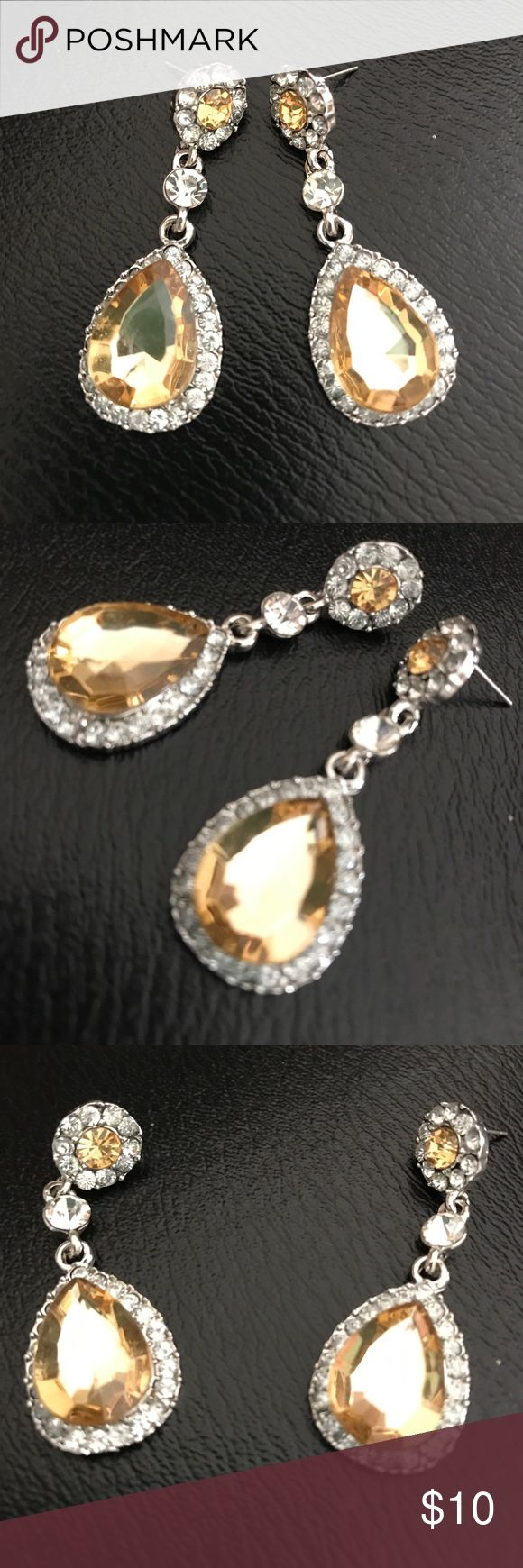 Beautiful new amber rhinestone teardrop earrings🔥 Beautiful new silver colored earrings with center teardrop amber colored stone as well as Amber center stone in top teardrop surrounded by rhinestones as well as top round portion of hearing beautiful on would look great with any outfit casual or formal Jewelry Earrings