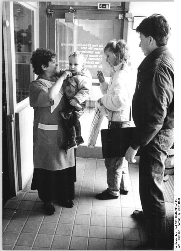 Berlin, Marzahner Tor, Kaufhaus, Kinderbetreuung - 5.3.90:  Einkaufsbummel- Yvette Goeschke und ihr Ehemann Jörg- beide von Beruf Ökonom- nehmen im Warenhaus Marzahner Tor gern einen speziellen Kundendienst in Anspruch: die Kinderbetreuung. Mitarbeiterinnen des Warenhauses kümmern sich während der Kundeneinkäufe um die Kleinen im Alter von 6 Monaten bis zu 6 Jahren in einem freundlich eingerichteten Kinderspielzimmer. Auch eine Kinderwagenaufbewahrung ist vorhanden.