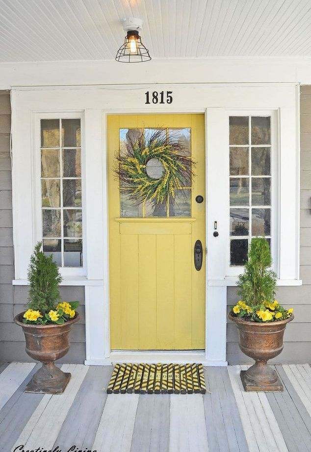 yellow farmhouse front door on a gray house