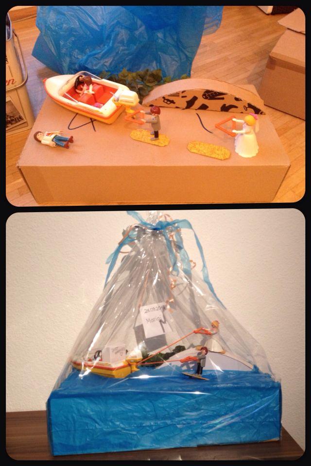 Geschenk zur Hochzeit. Das Geld befand sich in dem Kästchen, welches sich auf der Rückbank des Bootes befindet. Der Hochzeitsantrag hat auf einer Wakeboardanlage stattgefunden.   Material: Karton, weiße Pappe, Wolle,  Holzspieße, Müllbeutel, Playmobil Boot, Playmobil Hochzeitspaar, Dekopatch für die Boards aus Pappe, Heißklebepistole