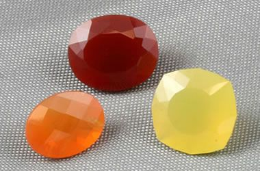 """FIRE OPAL <> """"Fire Opal"""" is a term used for colorful, transparent to translucent opal that has a bright fire-like background color of yellow, orange or red. It may or may not exhibit a """"play-of-color"""". The color of fire opal can be as vivid as seen in the three stones shown in the photograph at right."""