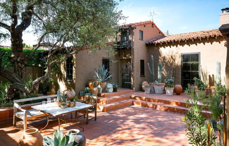 Container gardens of cacti look right at home in thered-tiled outdoor living room.