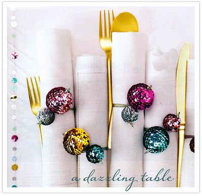Wrap 2 foam balls with strung sequins, and thread 1/4-inch metallic ribbon through them using a tapestry needle; wrap the ribbon around the napkin, then tuck the smaller ball through to hold it in place. Sew sequins by hand along a runner's hemstitching for a confetti effect.