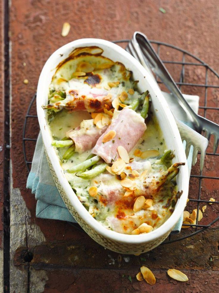 Bereiden: Warm de oven voor op 200°. Kook de boontjes in gezouten water net niet gaar. Rol in elk half sneetje ham enkele boontjes. Leg in een ovenschaal. Kruid de rolletjes met selderzout en peper. Hak de peterselie fijn. Snijd de mozzarella in plakjes. Smelt de boter in een pot, voeg hieraan de bloem toe en meng tot een homogeen geheel. Voeg er 2/3 van de melk aan toe en roer tot een gladde saus. Voeg nu al roerend beetje bij beetje de resterende melk toe.