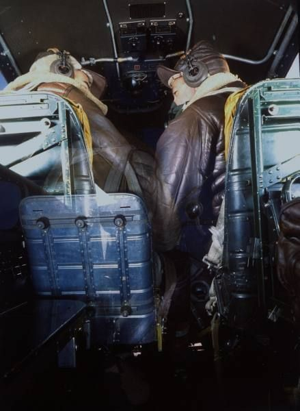 Fortune Color February 1942. Rear view of 2 pilots wearing US mil. leather flight suits & oxygen masks talking as they sit side-by-side in plane cockpit (no caps). | Date: 1942 | Photographer: Dmitri Kessel | LIFE archive - Hosted by Google