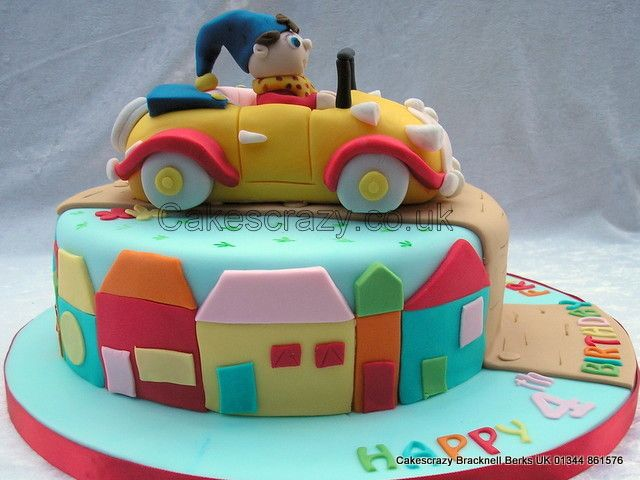 Novelty Noddy cake with Noddy character in his cake modelled from sugar and mounted on top of a round cake. The sides are decorated with sugarpaste houses  http://www.cakescrazy.co.uk/details/noddy-cake-1.html