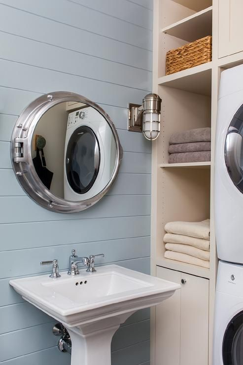 Cottage pool house bathroom with blue shiplap walls mounted with a nautical porthole medicine cabinet over a white pedestal sink beside a cream shelving unit fitted with a stacked washer and dryer.