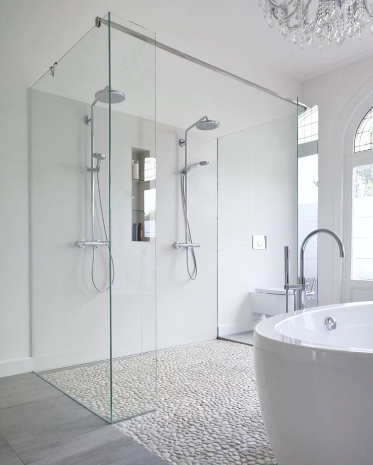 Modern bathroom features a crystal chandelier free standing acrylic tub a mix of marble tile and pebble floor and a double shower with custom made glass panels. by roomporn #ModernBathroom