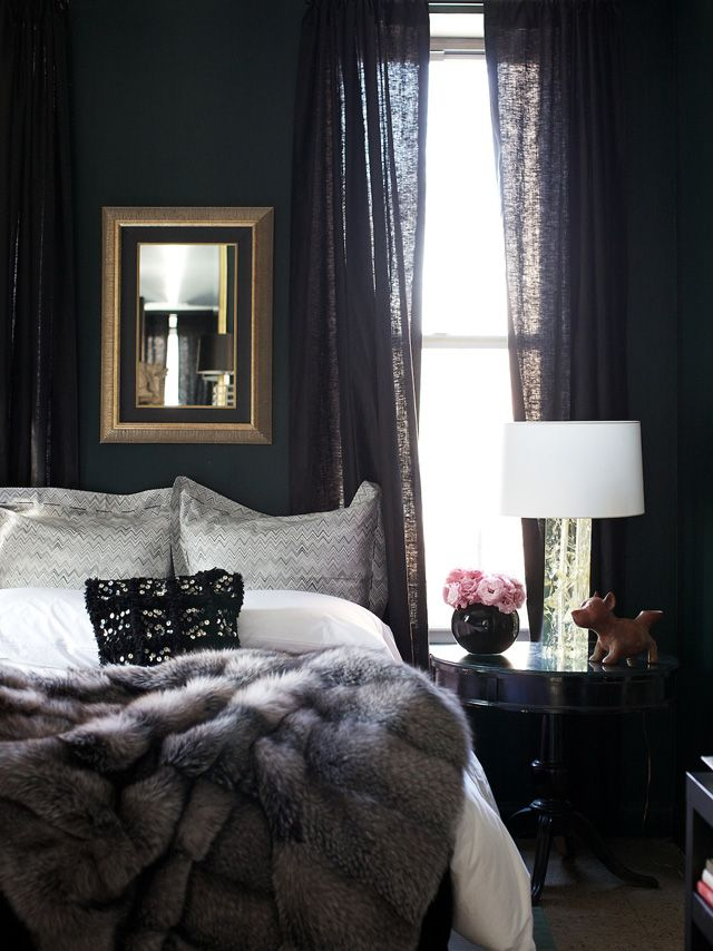 beautiful dark and cozy bedroom painted black with white bedding and a gray faux fur throw blanket
