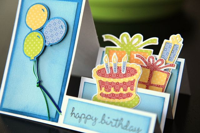 "handmade birthday card ... side step design ... Cricut cutting files ... balloons on thin ribbon string ... birthday cake with candles ... packages ... ""happy birthday"" stamped on panel on the first step ... delightful card!!"
