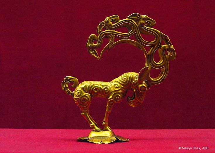 Han Dynasty  汉代  Gold Mythical Beast  金怿兽 This object has the characteristics of a deer, a horse, a bit of donkey, and additional birds and beasts are included in the antlers and tail. It is 4.53 inches tall (11.5 cm). It dates to the Han Dynasty period (206 BC - 220 AD). It was found in 1976 at a site in Shenmu County. It is probably a product of the Xiongnu culture that occupied the Shenmu area. The Xiongnu were considered to be very fierce by the Chinese.