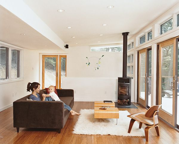 """TAKE ME HOMEA """"tree house"""" of clean lines, ample glass, and thoughtful ingenuity lets a Washington, DC–area family and a stream of weekend guests enjoy prefab living in an unlikely locale: just outside Lost River, West Virginia. A Movie sofa, by CB2, and a Rais wood-burning stove are in the living room.Photo by Chris Mueller.  Photo by: Chris Mueller"""