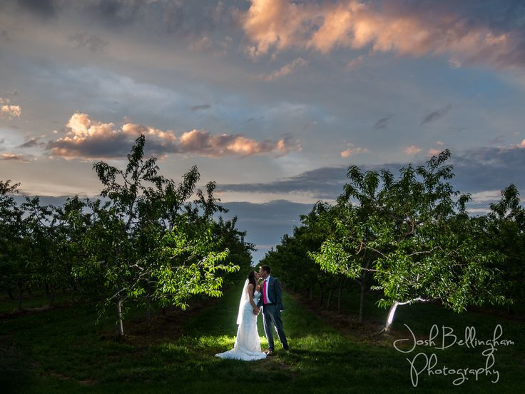 Incredible photograph with a dramatic colorful sky and a stunning bride and groom kissing in beautiful Orchard Croft. #JoshBellinghamPhotography