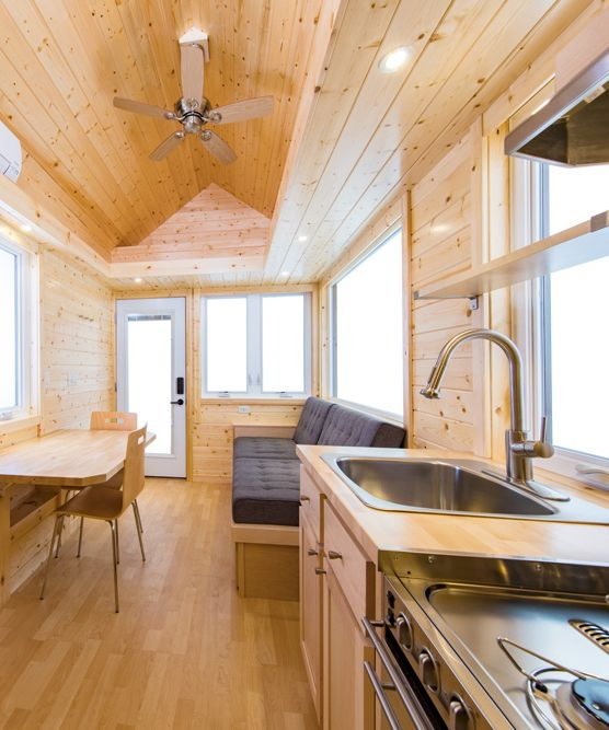 The kitchen is equipped with a gas or induction cook top, full size refrigerator, and optional stainless LP range and hood. The kitchen also has maple cabinetry, a stainless sink, designer faucet, and a butcher block kitchen table.